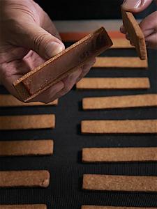 スパイスを配合したクッキーでビターキャラメルをサンドするのも手作業。